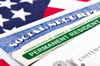 What do you call a person who has been granted authorization to live and work in the United States on a permanent basis, but is not eligible for certain benefits, such as voting and some social services?